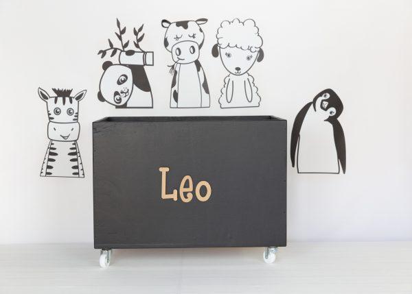 Monochrome animals with large black toybox on wheels